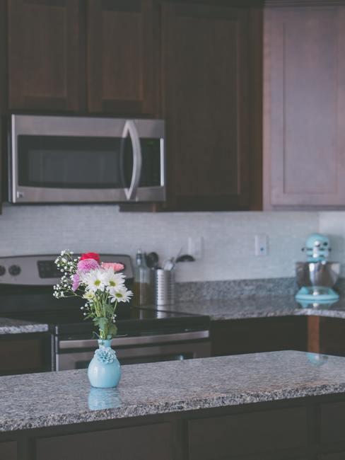 Oven schoonmaken: keuken met houten meubelen en een blad in marmerlook en vaas met bloemen