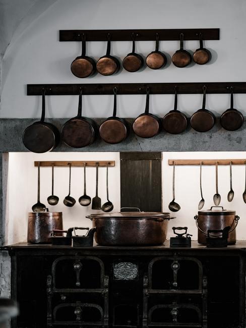 Frituurpan schoonmaken: diverse pannen hingen aan haken in de keuken