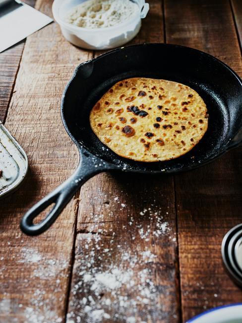 Frituurpan schoonmaken: koekenpan op een houten tafel