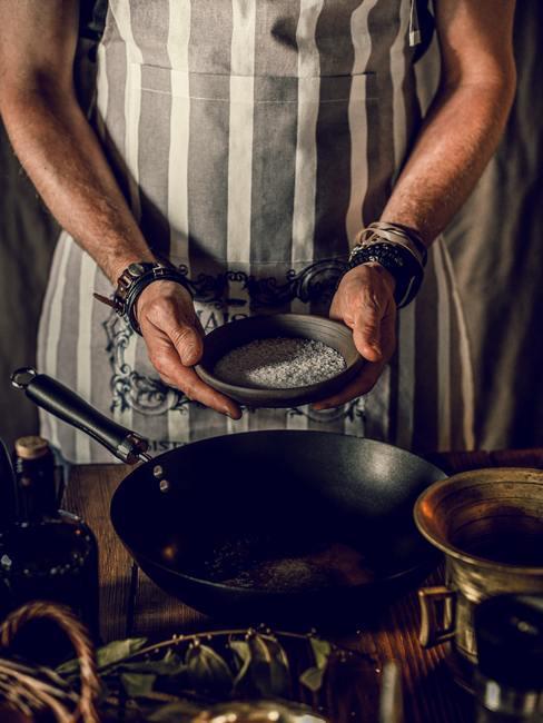 Een man die een maaltijd in een schone koekenpan bereidt