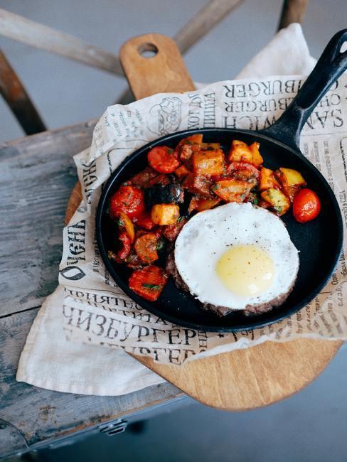 Gebakken groenten en een gebakken ei in een pan op een snijplank