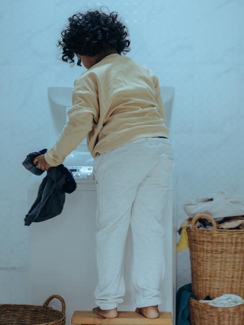 Kind in witte broek en gele blouse vult witte wasmachine met kleren
