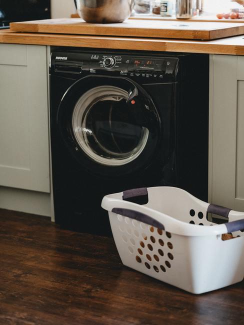 zwarte wasmachine met witte wasmand ervoor