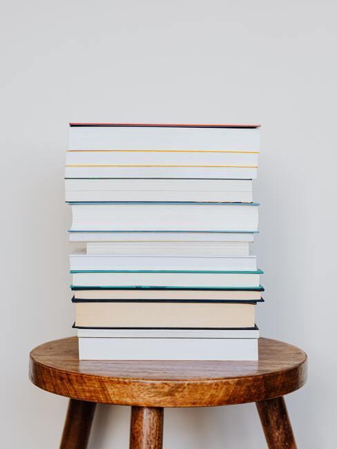 stapel leesboeken op een houten kruk