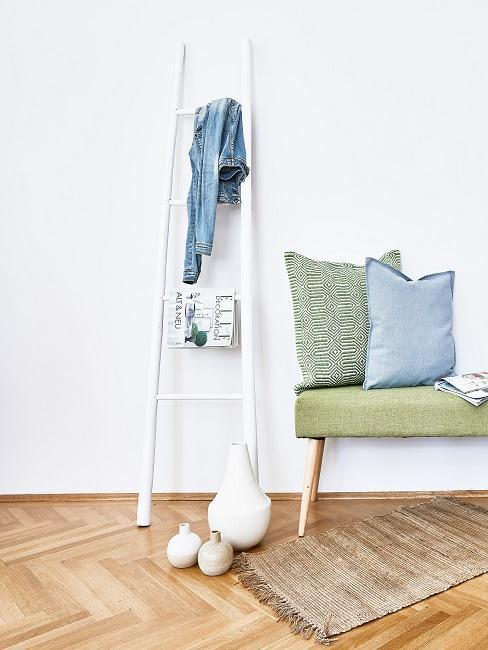 Witte ladder en groene zitbank voor witte muur