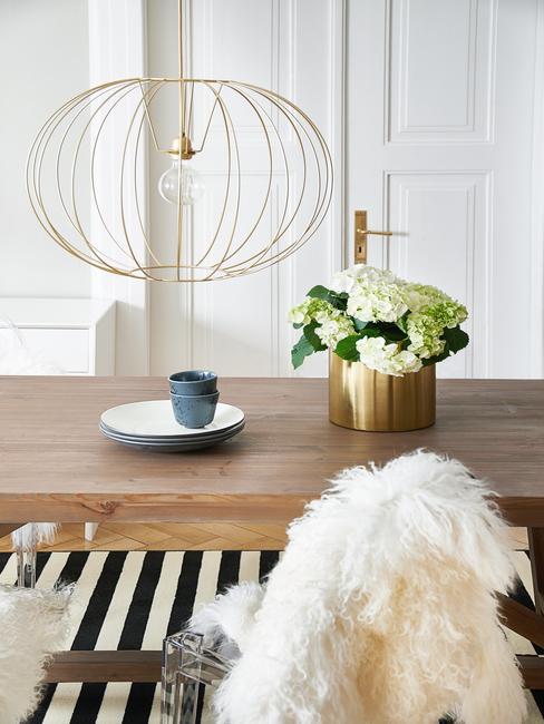 Eettafel met vaas met bloemen en decoratief bord, goudkleurige hanglamp en zwart en wit gestreept vloerkleed