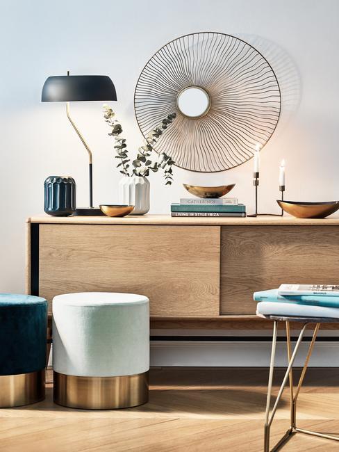 Houtsoorten: moderne woonkmaer met houten sideboard met verschillende accessoires en ornamenten en zwarte tafellamp naast fluwelen kruk