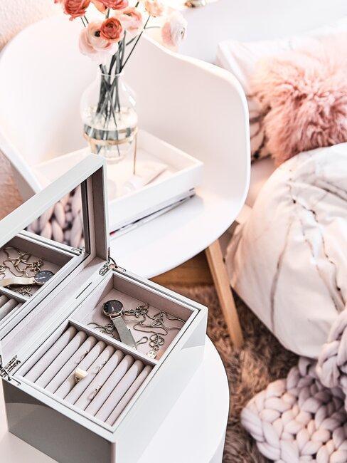 witte stoel met roze bloemen en grijze sieradendoos