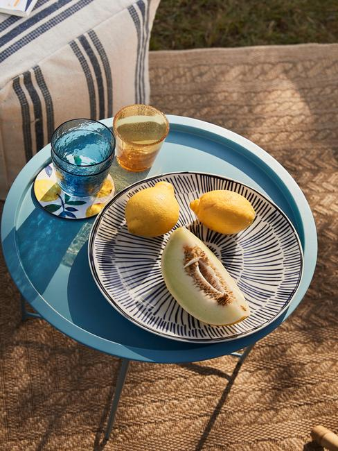 blauw tafeltje met fruit en blauwe en gele glazen
