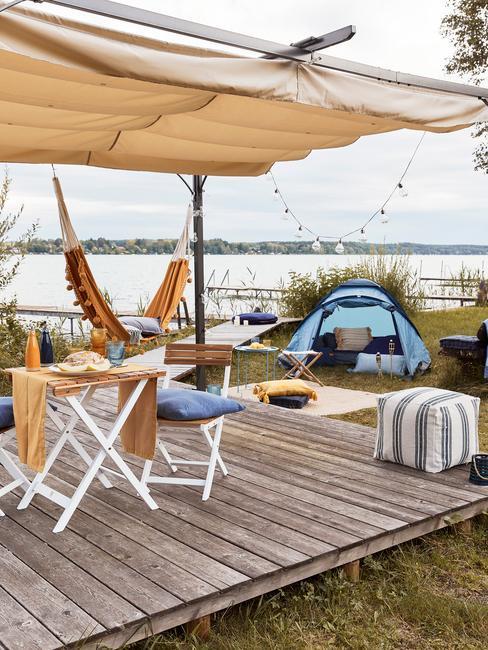 glamping met een houten vlonder en een blauwe tent