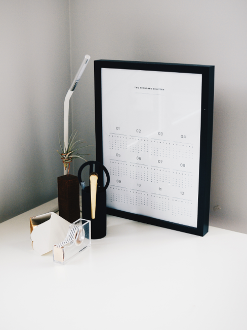 Kalender, lamp en kantoorartikelen voor grijse muur op witte tafel