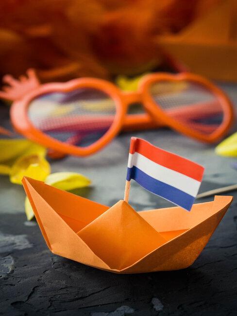oranje zonnebril en papieren bootje met nederlands vlaggetje