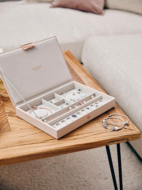 Sieraden doos op houten salontafel en zandkleurige bank