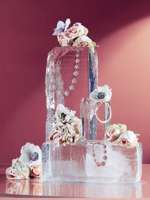 Roze wand met bloemen en sieraden op onbewerkte blokken ijs