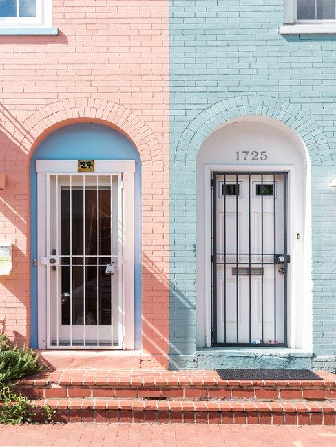 Gevel met twee witte deuren en blauwe en roze bakstenen