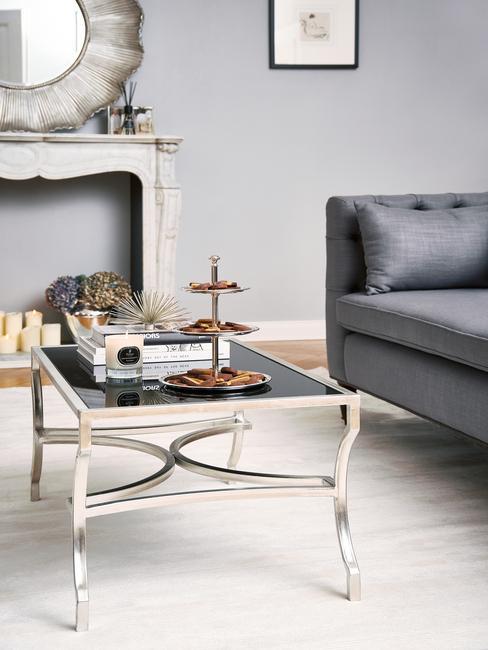 Zitbank in grijs naast een zwarte salontafel