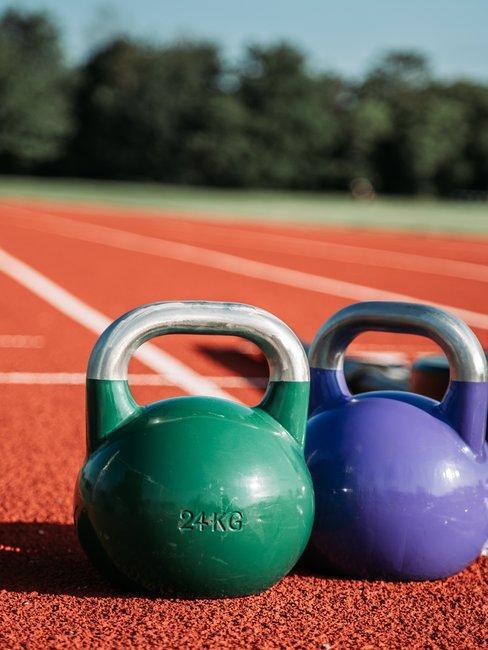 Groene en paarse kettebals op atletiekbaan