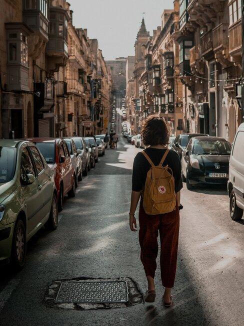 jongen met rugzak loopt door een stad