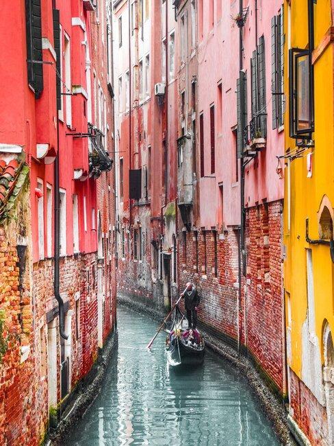 gekleurde woningen aan een gracht in venetie met een gondel