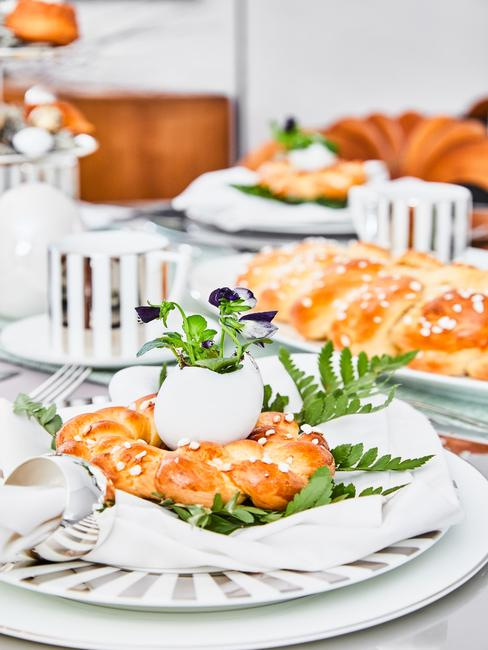 Tafelsetting pasen met paasei en brood op wit servies