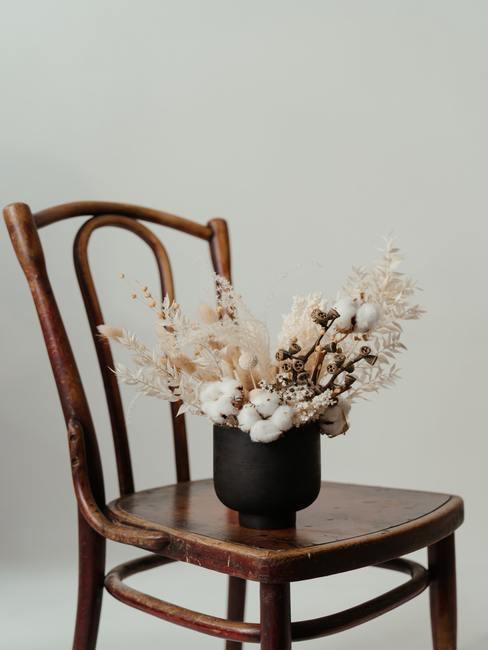 Een boeket gedroogde bloemen in een zwarte lage vaas op een houten stoel in de boho-stijl