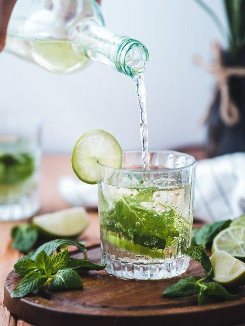 Glas met water en groene muntbladeren op houten ondergrond en een glazen fles die water inschenkt