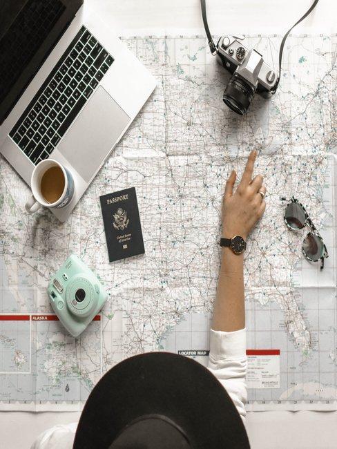 Lankaart met laptop paspoort zonnebril camera van boven gefotografeerd met arm en hoed