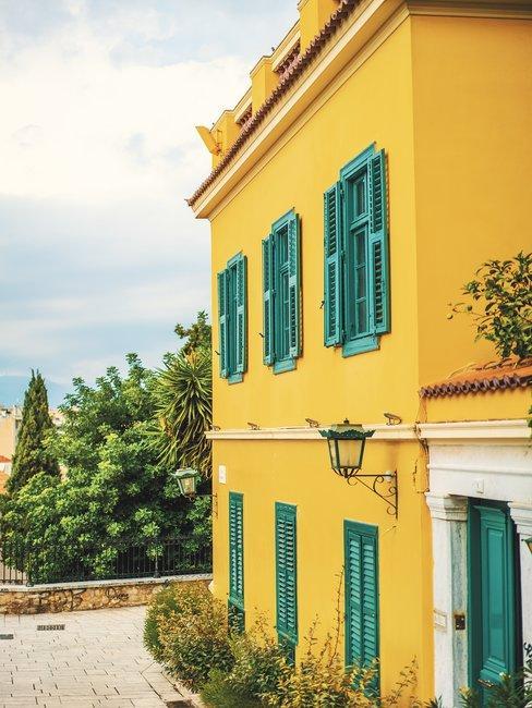 Zij aanzicht van een geel huis met groene luiken en bomen