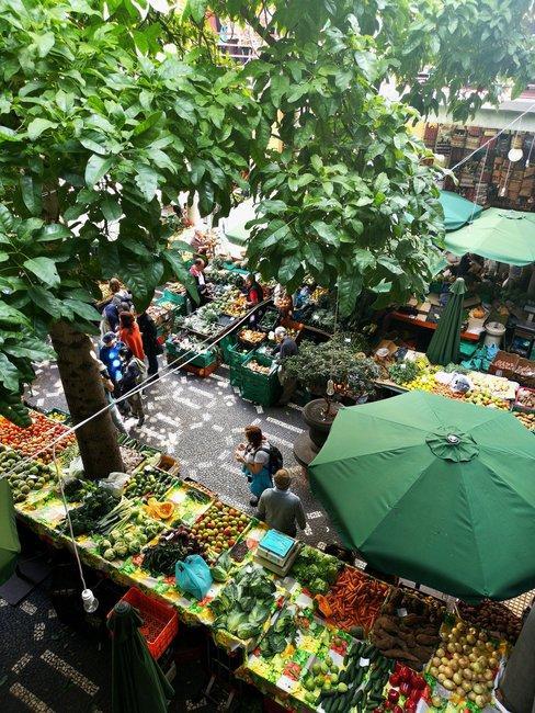 Fruitmarkt van boven met groene parasol en bomen gefotografeerd