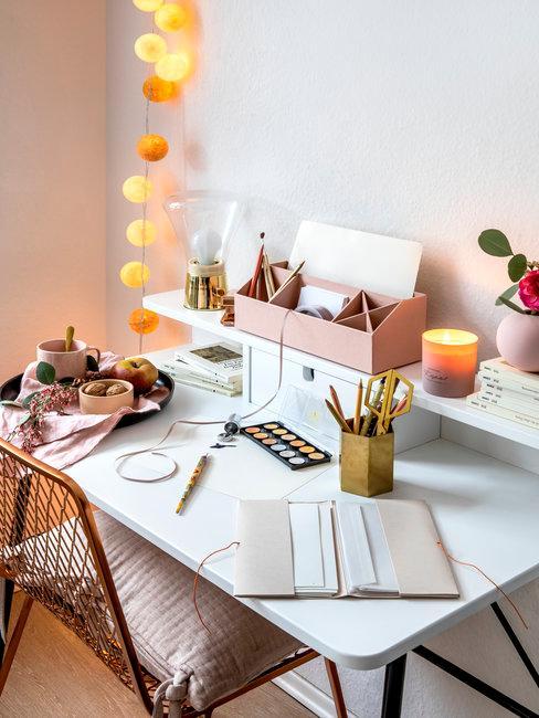 Wit bureau met kantoormaterialen en oranje lichtslinger en bronze bureaustoel met roze kussen