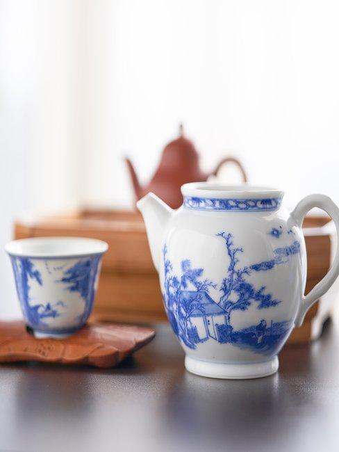 Delfts blauwe theepot met kopje op hout met witte achtergrond