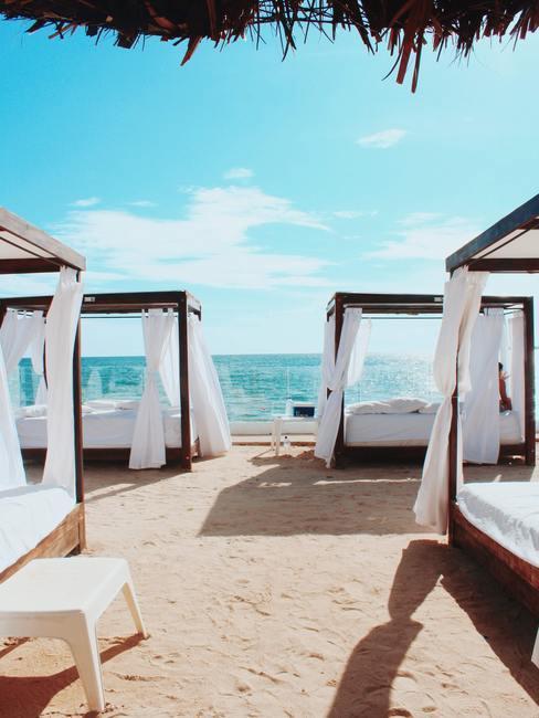 Hemelbedden op een wit zandstrand met blauwe zee