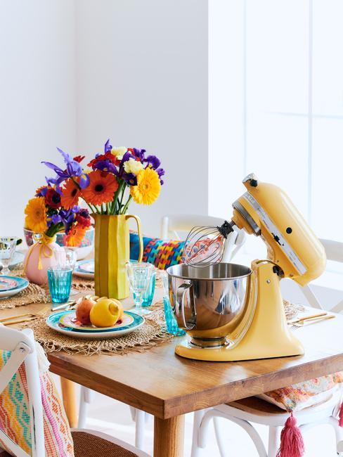 Vaas in geel met bloemen op eettafel naast glazen