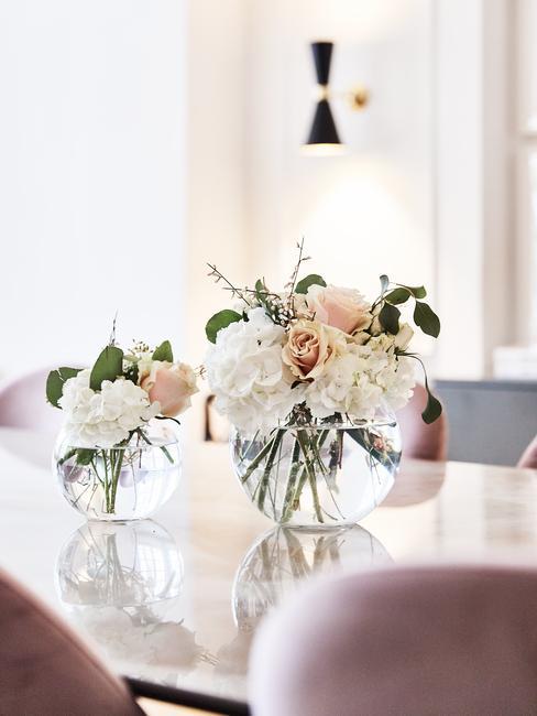 Transparante glazen vaas met bloemen op eettafel