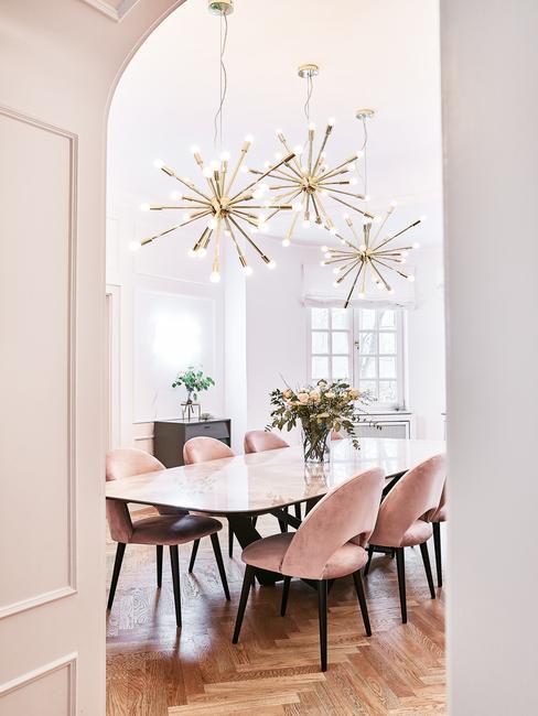 Fluwelen stoelen in roze en hanglamp in goud kleur
