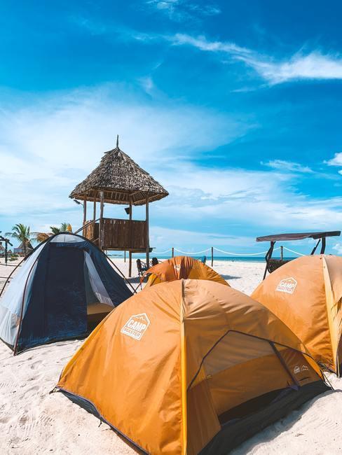 Camperen op het strand in gele tenten met een blauwe lucht