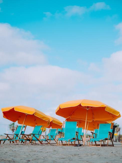Gele parasols met licht blauwe strandstoelen op het strand met een helder blauwe lucht