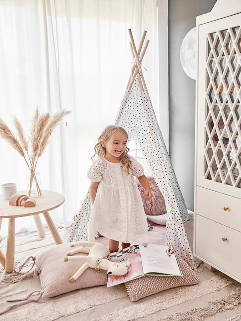 Meisje voor een tipi tent in een kamer met witte kast en lichte kamer