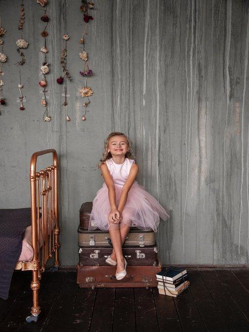 Kind in balerina jurk op stapel oude leren koffers naast het bed