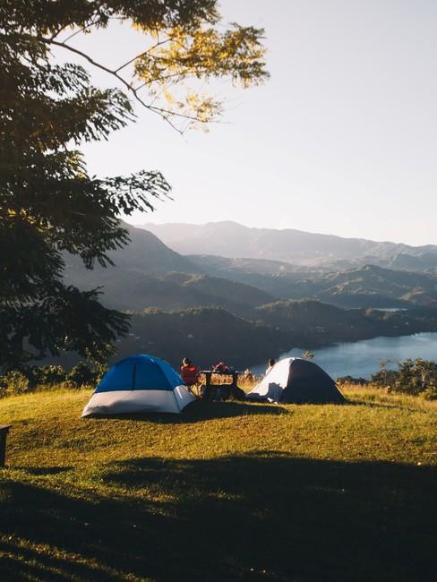 Tenten op een heuvel met uitzicht over een meer en bergen