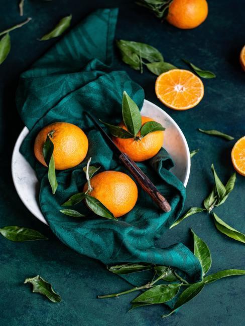 Sinaasappelen in witte schaal op donkergroene ondergrond