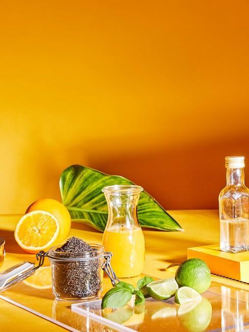Setting voor het persen van sinaasappelsap voor een oranje muur en tafel