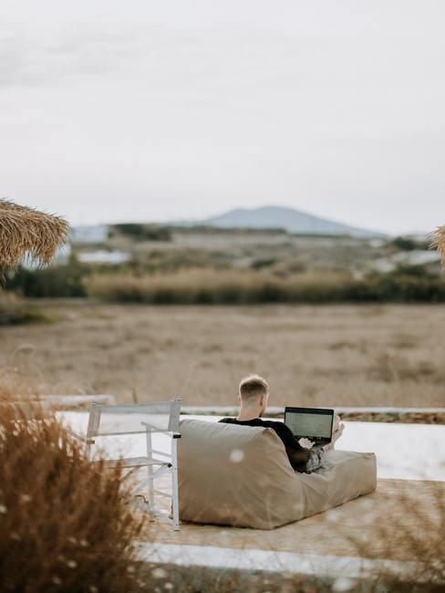 Man op beige loungebank in tuin met uitzicht op bergen
