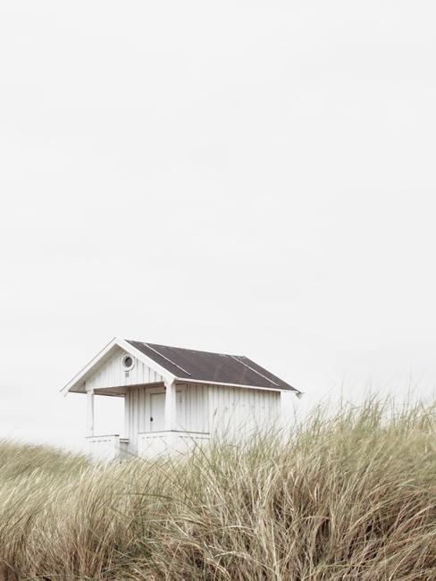 Wit houten huis in de duinen met grijze lucht