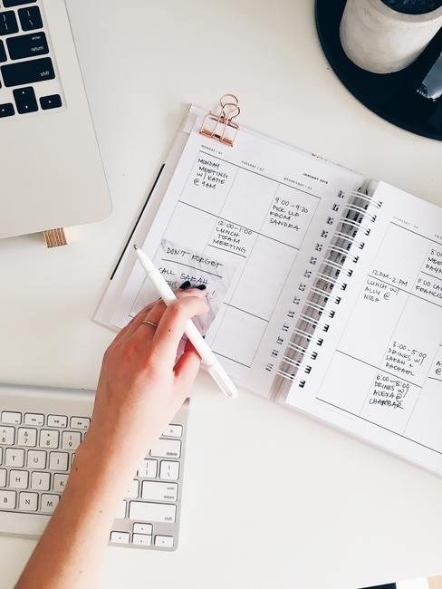Witte tafel met laptop en toetsenbord en huishoudboekje met hand