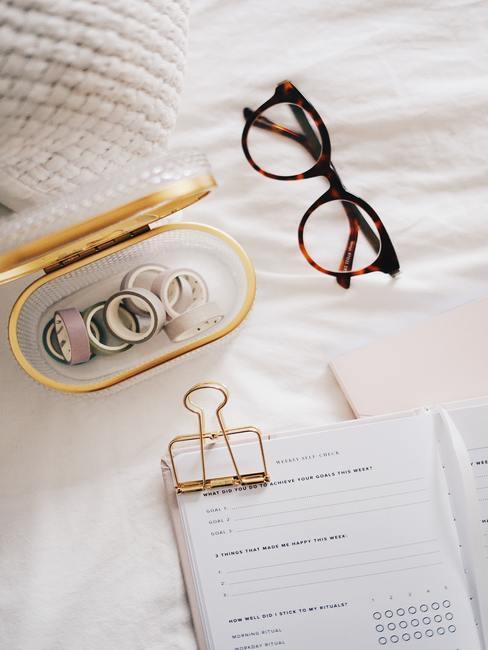 Witte lakens met notitieboekje bruine bril en pennendoosje