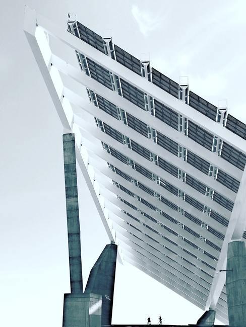 een rij met zonnenpanelen tegen betonnen palen