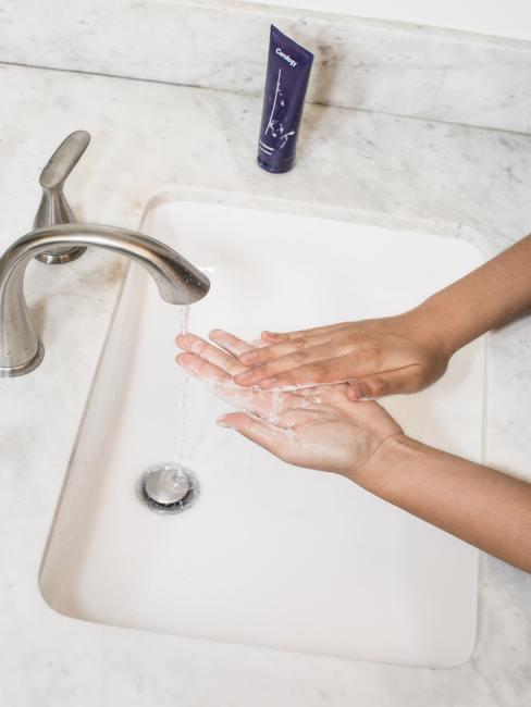 Handen wassen onder marmeren tafel