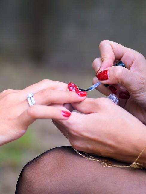 Twee handen die rode nagellak aanbrengen bij elkaar