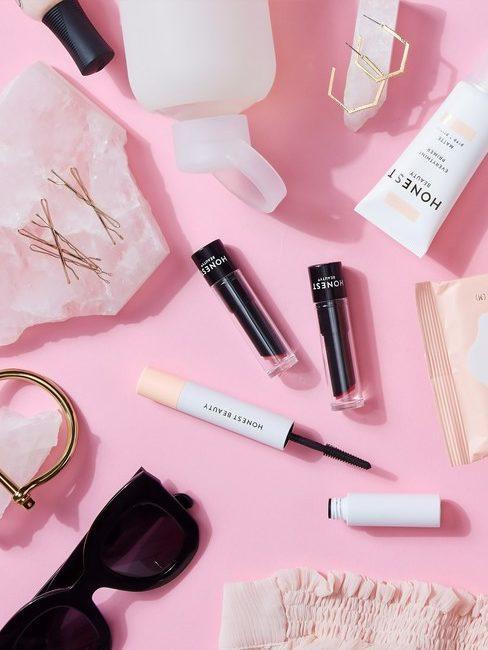 Roze achtergrond met make up zonnebril en tubes